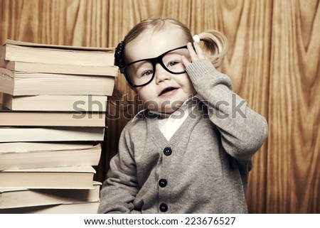 Young girl in glasses next to stack of books - stock photo