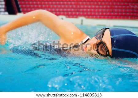 young girl in goggles and cap swimming crawl in the pool - stock photo