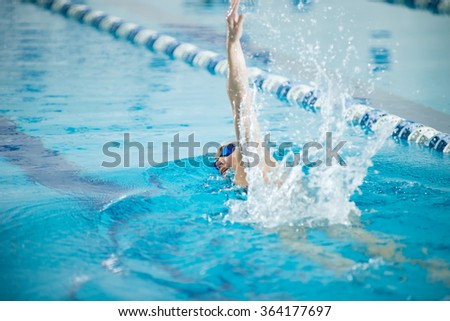 Young girl in goggles swimming front crawl stroke style - stock photo