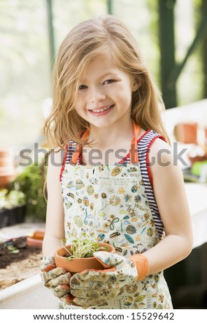 Young girl in greenhouse holding potted plant smiling - stock photo