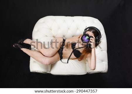 Young girl in lingerie lying on white chair with vintage headphones, holding a new  generation reflex camera while taking a picture. Caucasian sensual female photographer. View from above. - stock photo
