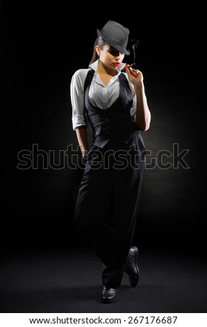 Young girl in manly style with cigar on black - stock photo