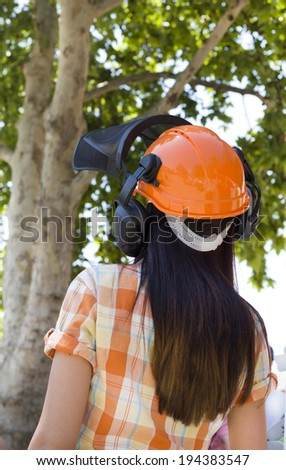 Young girl in plaid shirt wearing orange helmet with earphones from back - stock photo