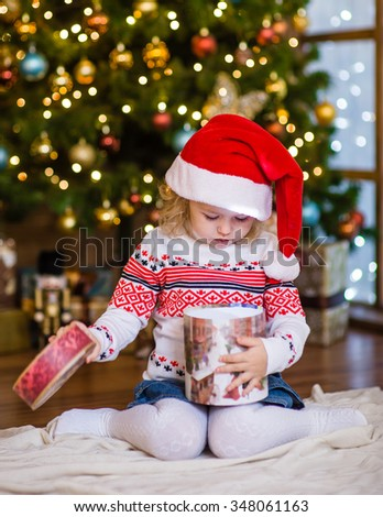 Young girl  in red santa hat opening Christmas gifts - stock photo