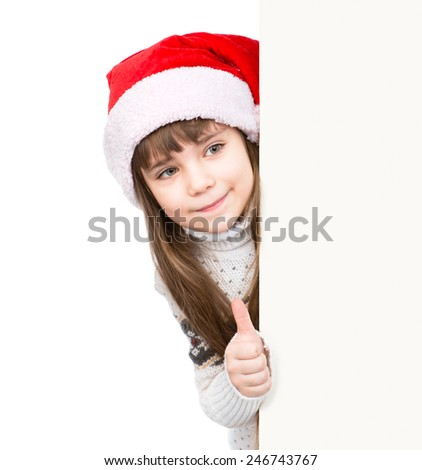 young girl in red santa hat standing behind white board and showing thumbs up. isolated on white background - stock photo