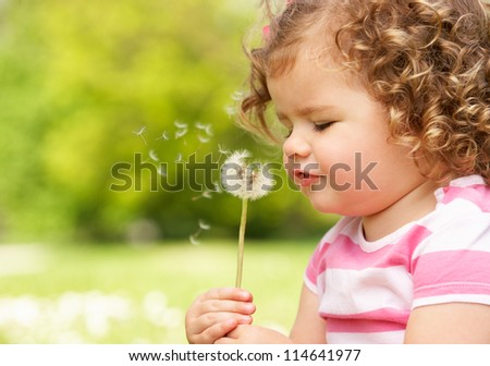 Young Girl In Summer Dress Sitting In Field Blowing Dandelion - stock photo