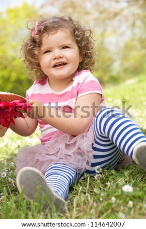 Young Girl In Summer Dress Sitting In Field Wearing Straw Hat - stock photo