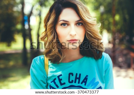 young girl in sweater posing on the street, the portrait mood, sweet woman, a stylish young modern girl pretty hair well-groomed outdoor portrait, close up posing in the park - stock photo
