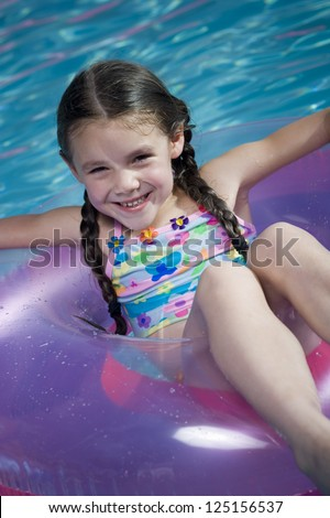 Young girl in swim ring in a swimming pool - stock photo