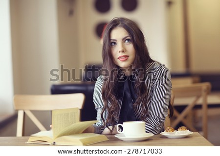 young girl in the cafe, book, reading, coffee - stock photo
