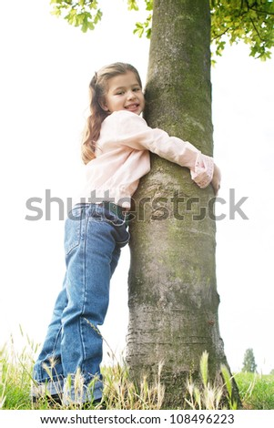 Young girl in the park hugging a tree on a hill, against the sky, and smiling to camera. - stock photo