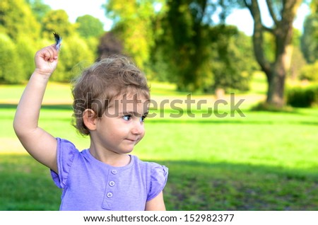 Young girl in the park, wearing a purple / lavender t-shirt holding a feather with her arm stretched above her head. - stock photo