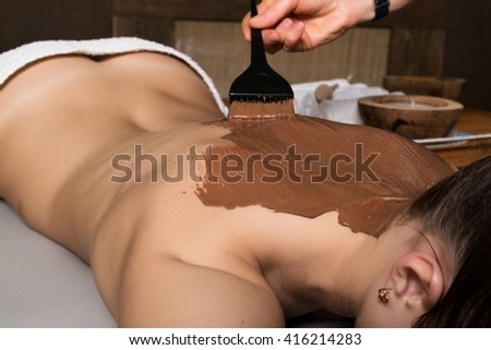 young girl in the spa salon, chocolate body wrap treatment, skin rejuvenation. Beauty treatment concept - stock photo