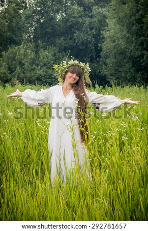 young girl in the Ukrainian embroidered shirt, with a wreath of flowers on her head, standing barefoot on the grass in the field under the shining sun - stock photo