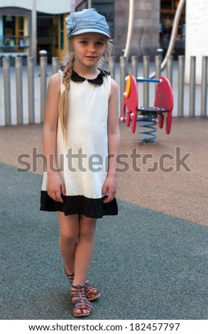 Young girl in white dress and denim cap on the playground - stock photo