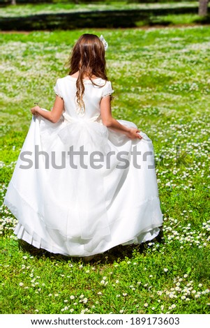Young girl in white dress walking in flower field. - stock photo