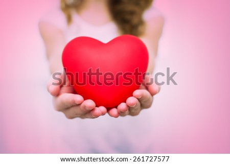 young girl in white shirt with l red heart - stock photo
