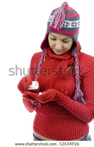 young girl in winter hat pouring out tablets, drugs, on palm - stock photo