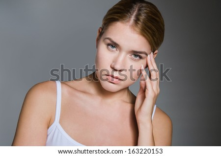 young girl in worry touching her head, on dark background - stock photo