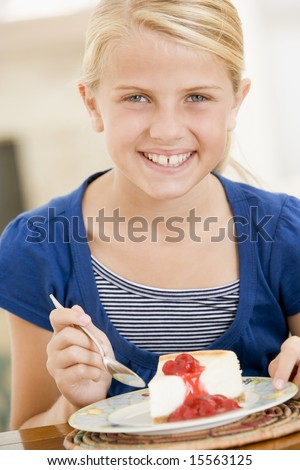Young girl indoors eating cheesecake smiling - stock photo