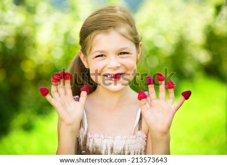 Young girl is holding raspberries on her fingers, outdoor shoot - stock photo