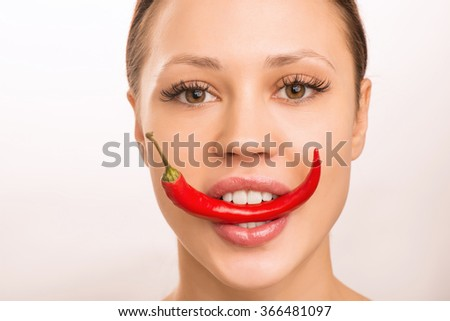 Young girl is holding red pepper with her teeth. - stock photo