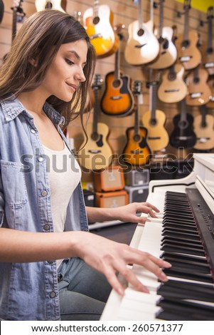 Young girl is playing piano in a music store. - stock photo