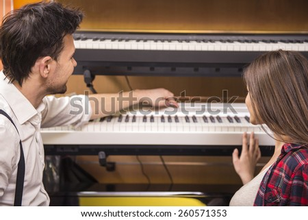 Young girl is playing the piano with man in the music store. - stock photo