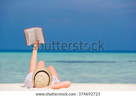 Young girl is reading a book lying on tropical white beach - stock photo