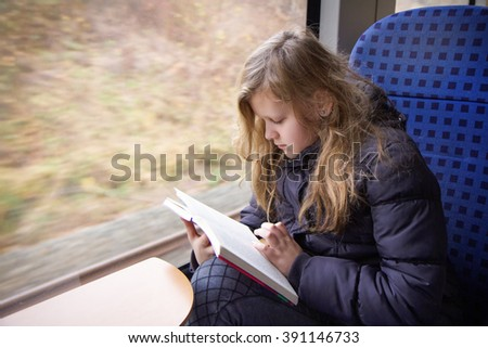 Young girl is reading a book while traveling by train - stock photo
