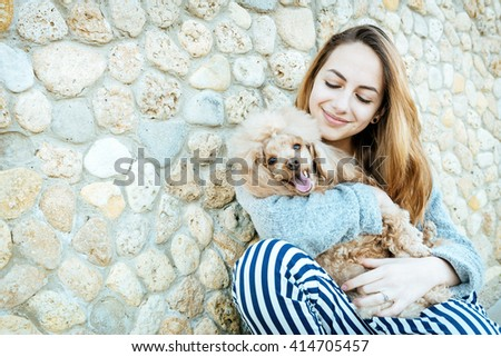Young girl is resting with a dog on the outdoors. - stock photo