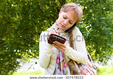 Young girl is talking by phone on the street on background of green foliage in summer, phone is pressed between her ear and shoulder, and girl is writing some information by pencil at sheet of paper - stock photo
