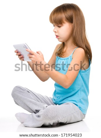 Young girl is using tablet while sitting on floor, isolated over white - stock photo