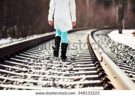 Young girl is walking in the railroad tracks. Image taken during spring time and there is some snow left on the ground. Image has a vintage effect applied. - stock photo
