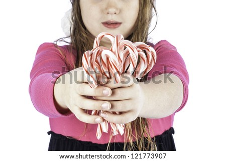 young girl isolated on white with her hand outstretched holding candy canes - stock photo