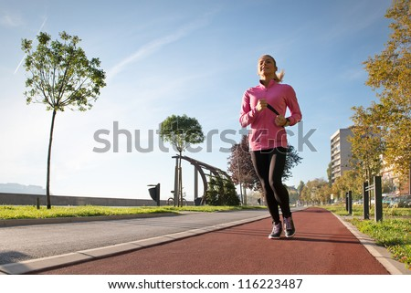 young girl jogging outdoor along trees path - stock photo