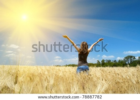 young girl joys on the wheat field at the bright sunny day - stock photo