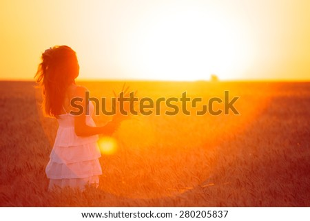 young girl joys on the wheat field at the sunset time - stock photo