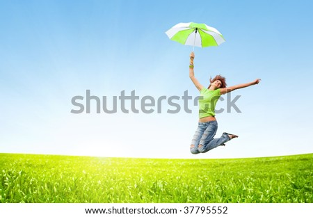 young girl jumping with umbrellas - stock photo