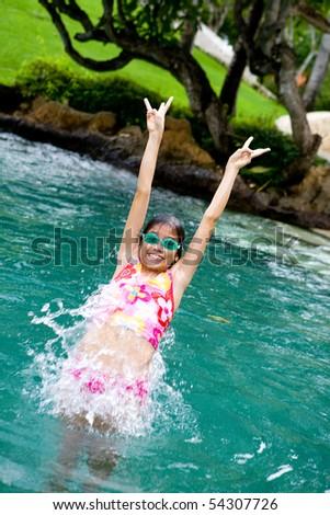 Young girl jumps backward into swimming pool - stock photo