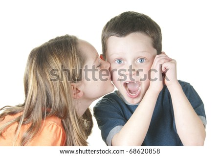 young girl kissing boy on cheek - stock photo