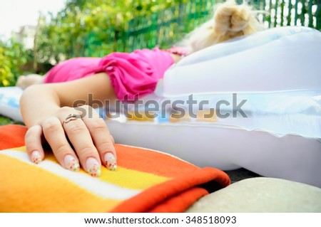 Young girl laying on mattress, focus on the hand - stock photo