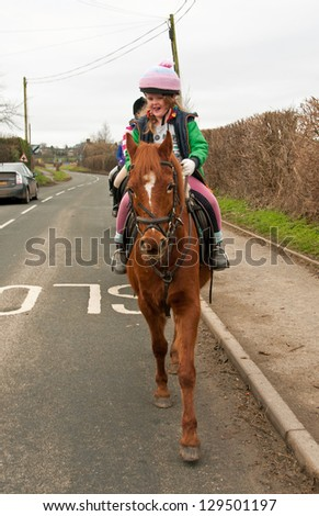 Young girl leading a group of horses down the road - stock photo