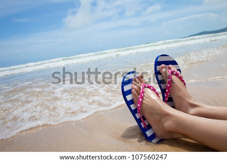 Young girl legs in colorful flipflop sandals on sea beach - stock photo