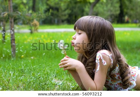Young girl lies on a grass with dandelions - stock photo