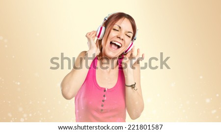 Young girl listening music over gloss background - stock photo