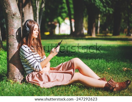 Young girl listening to music in city park - stock photo