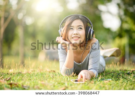 Young girl listening to music with headphone in city park - stock photo