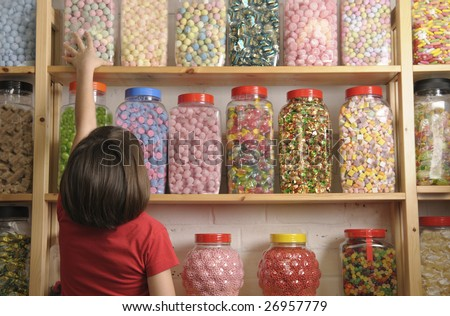 young girl looking at rows of sweets in shop - stock photo