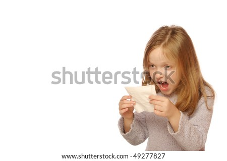 Young girl looking at tissue after blowing her nose - stock photo